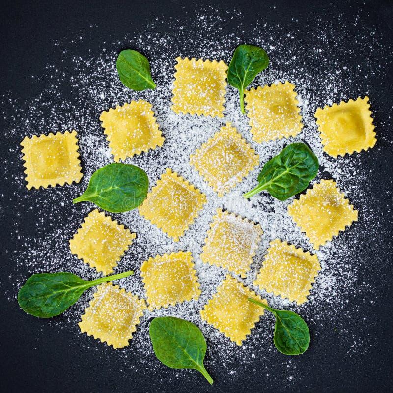 Ny raviolipasta med spenat, mjöl och örter på mörk bakgrund, bästa sikt Italienare Raviolli kopiera avst?nd royaltyfri foto