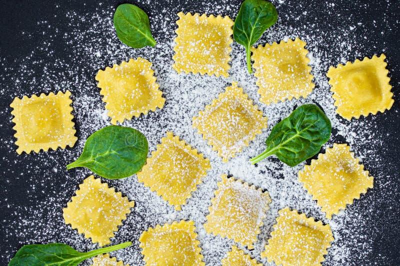 Ny raviolipasta med spenat, mjöl och örter på mörk bakgrund, bästa sikt Italienare Raviolli kopiera avst?nd arkivfoto