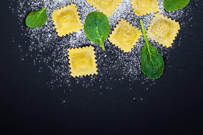 Ny raviolipasta med spenatsidor, mjöl och örter på svart bakgrund, bästa sikt Italienare Raviolli kopiera avst?nd arkivbild