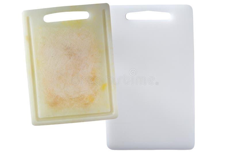Ny ren och smutsig vit plast- skärbräda med den mörka fläckskrapan som isoleras på vit royaltyfri foto