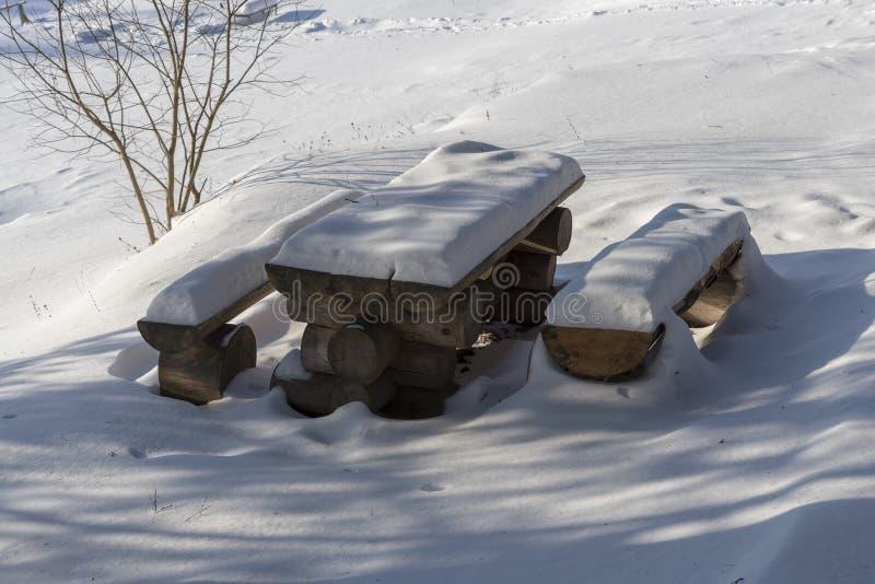 Ny ren snö som täcker brun mahognyträfärg, målade trädgårdstolar och den utomhus- tabellen fotografering för bildbyråer