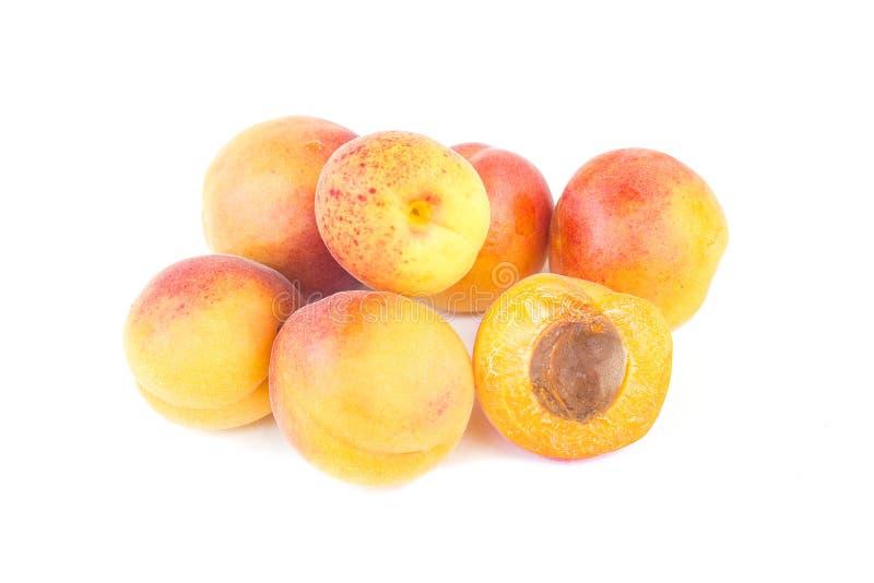 Ny söt aprikosfrukt, helt och halvt, grupp av den saftiga mogna aprikoscloseupen som isoleras på den vita bakgrunden arkivbild