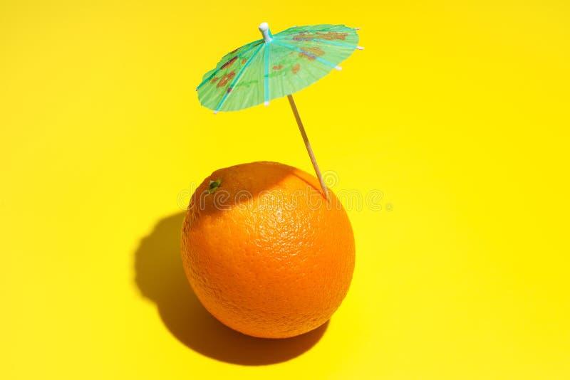 Ny saftig apelsin med ett coctailparaply som isoleras p? gul bakgrund Begrepp av sunt ?ta och att banta Drinkbegrepp arkivfoto
