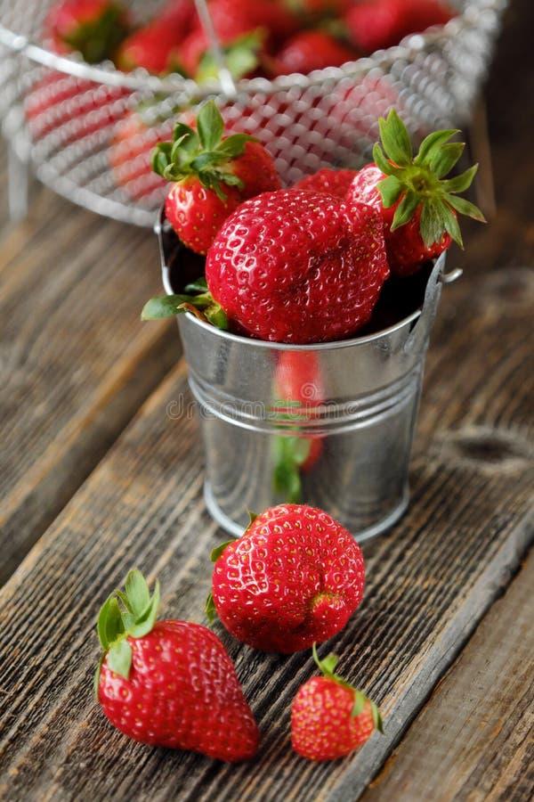Ny saftig jordgubbe i en liten hink på tabellen arkivfoto