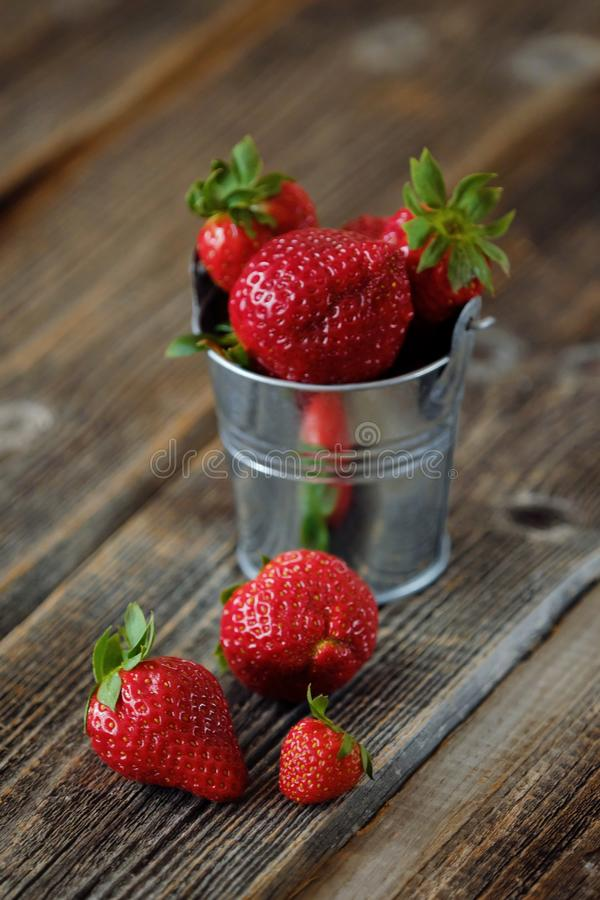 Ny saftig jordgubbe i en liten hink på tabellen royaltyfri fotografi