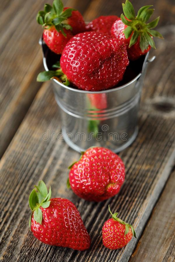 Ny saftig jordgubbe i en liten hink på tabellen royaltyfria bilder