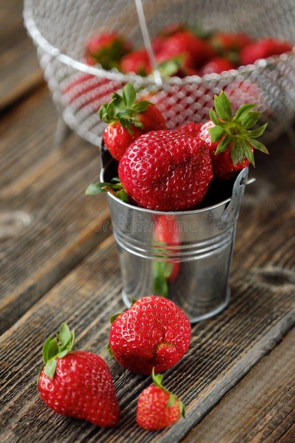 Ny saftig jordgubbe i en liten hink på tabellen royaltyfri bild