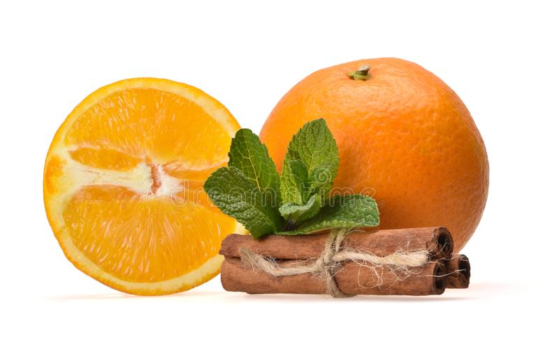 Ny saftig sammansättning av den mogna apelsinen, mintkaramellsidor, orange halvor och kanelbruna pinnar royaltyfria bilder