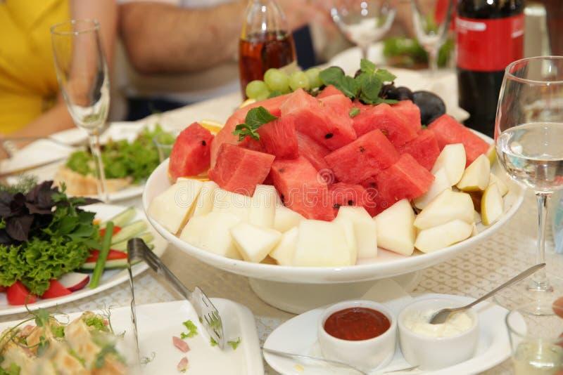 Ny sallad av den skivade röda vattenmelon och melon i en platta Ett exponeringsglas av drinken arkivbild