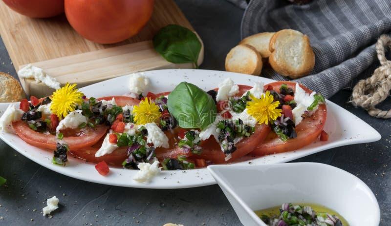 Ny sallad av tomater och mozzarellaen Recept med olivolja med den röda löken, oliv och basilika royaltyfria foton