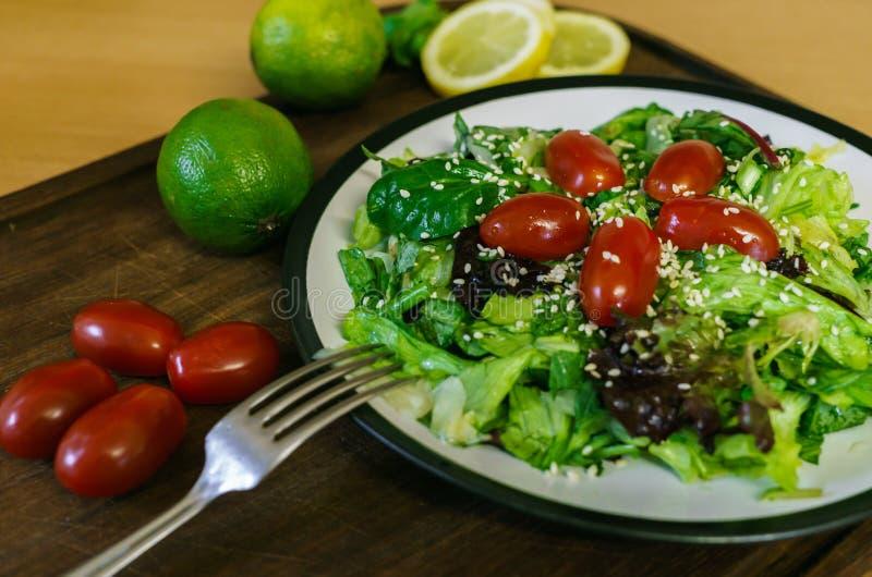 Ny sallad från olika sorter av gräsplaner och en körsbärsröd tomat, klädde med olivolja och strilat med sesamfrö arkivbilder