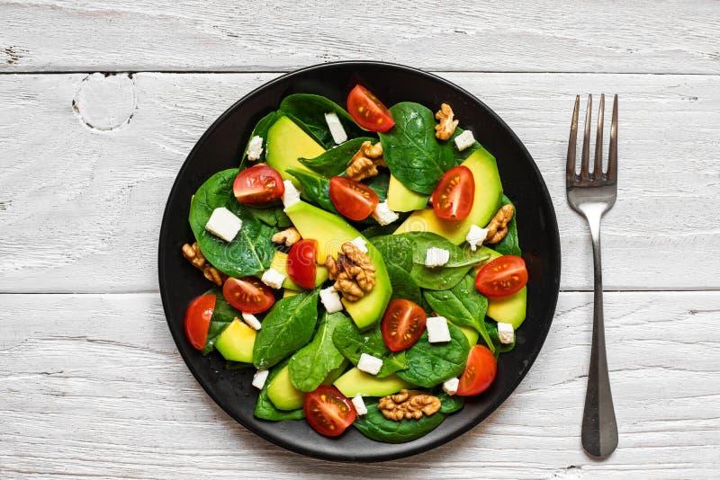 Ny sallad med avokadot, spenat, tomater körsbär, fetaost och valnötter i en platta med gaffeln på den vita trätabellen arkivfoton