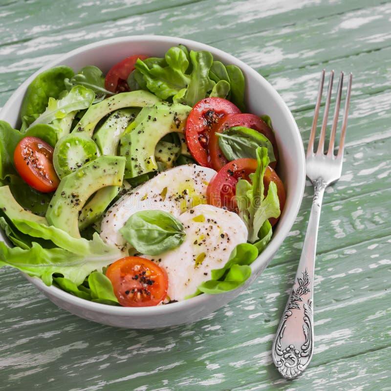 Ny sallad med avokadot, tomaten och mozzarellaen, i en vit bunke royaltyfria bilder