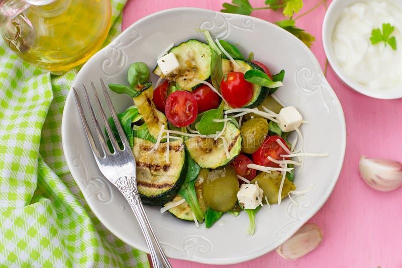 Ny sallad med den grillade zucchinin, ost, inlagda gurkor och körsbärsröda tomater arkivfoto