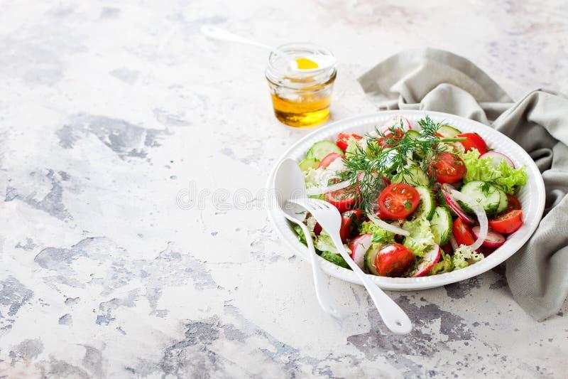 Ny sallad med körsbärsröda tomater, gurkor, rädisor, dill och olivolja arkivbild
