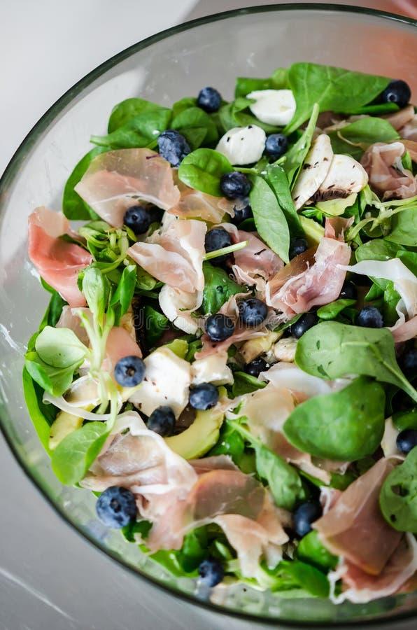 Ny sallad med lammgrönsallat, avokadot och prosciuttoen arkivbilder