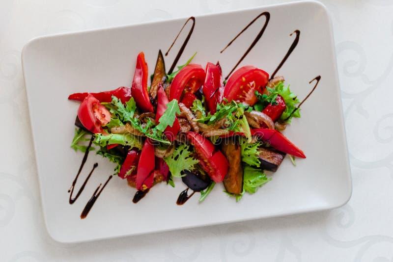 Ny salladplatta med aubergine, tomaten och blandad gräsplanarugula, mesclun, nära övre för mache sund mat Rent äta fotografering för bildbyråer