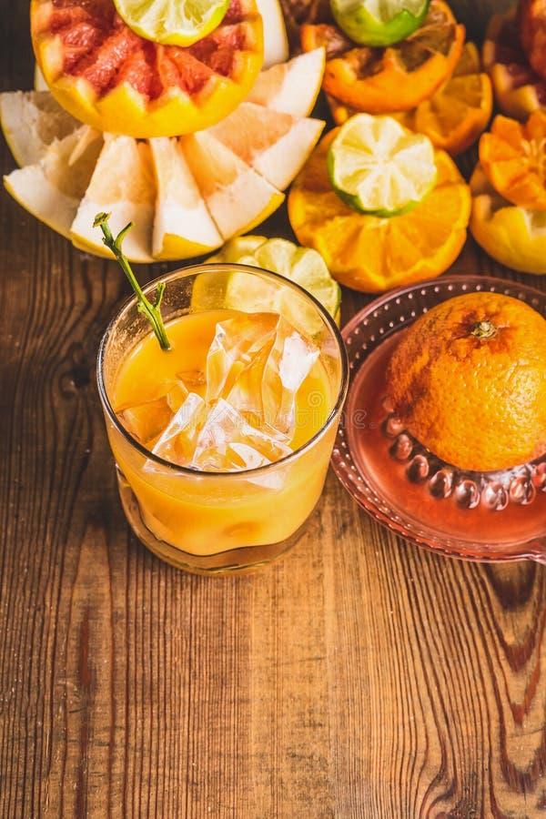 Ny sammanpressad citrus fruktsaft i exponeringsglas med iskuber på tabellen med ingredienser: apelsin citron, grapefrukt, mandari arkivbilder
