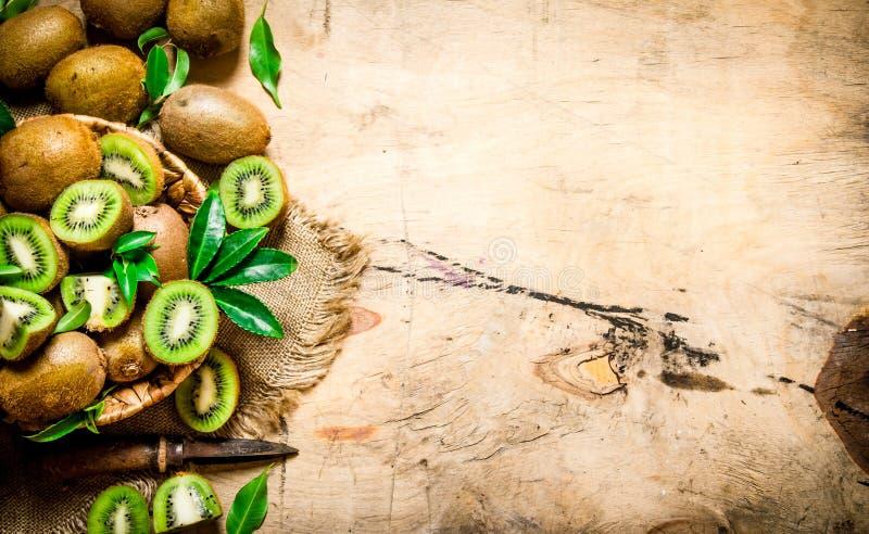 Ny skivad kiwi med en kniv och en full korg och sidor arkivbild