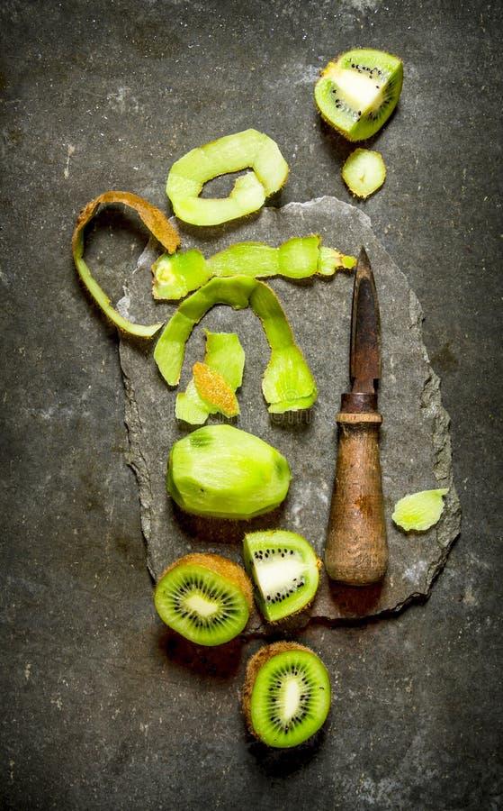 Ny skivad kiwi med en kniv på en stenställning royaltyfri fotografi