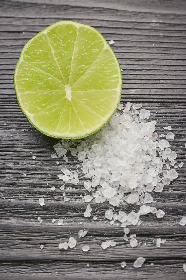 Ny skivad limefrukt och att salta på en trätabellcloseup halv limefrukt med saltar aptitretare för tequila royaltyfri foto