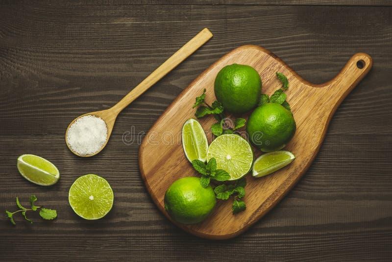 Ny skivad limefrukt och att salta på trätabellen arkivfoto