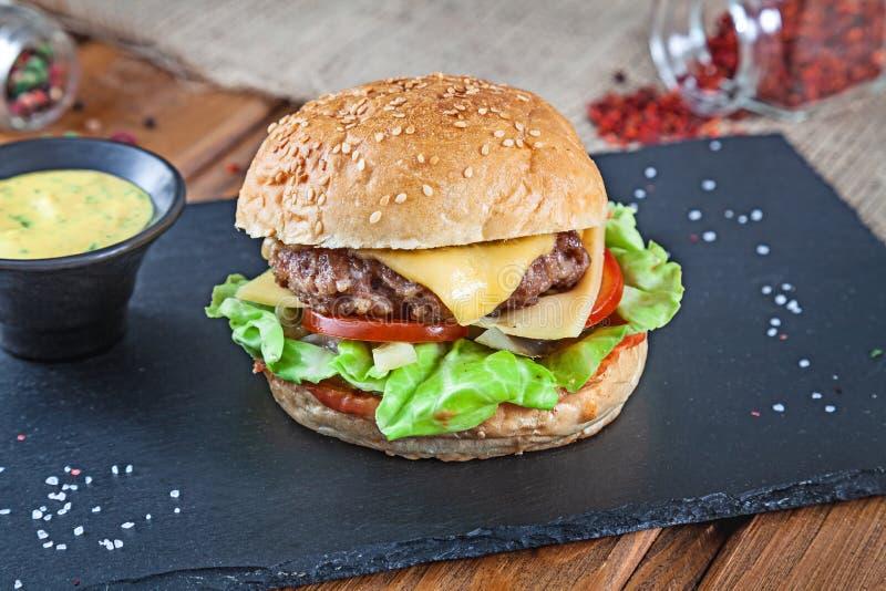 Ny smaklig hamburgare med ost, grönsallat, tomat, gurka på den svarta stenen med sås amerikanskt snabbmat Ostburgare med kopian arkivfoto