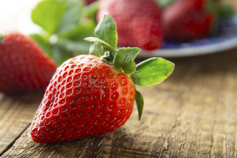 Ny smaklig sommarstrawberrie slut upp den mogna jordgubben på träbräde Ljus för sommardag fotografering för bildbyråer