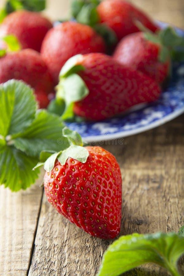 Ny smaklig sommarstrawberrie slut upp den mogna jordgubben på träbräde Ljus för sommardag arkivbilder