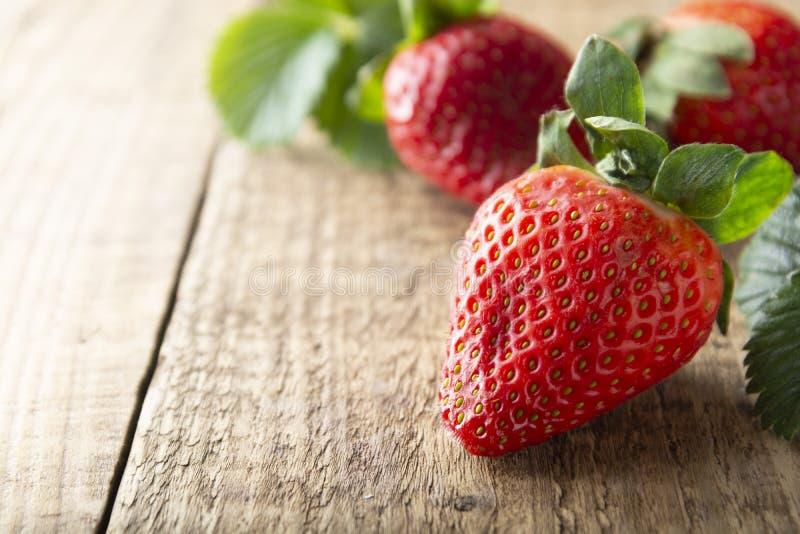 Ny smaklig sommarstrawberrie slut upp den mogna jordgubben på träbräde Ljus för sommardag royaltyfri foto