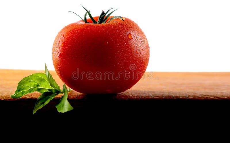 Ny smaklig tomat med det aromatiska basilikabladet arkivfoto
