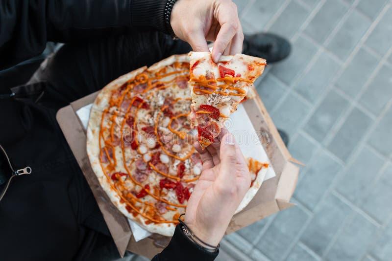 Ny smaklig varm pizza med korven med tomater med ost med sås i händerna av en man Stilfull grabb i svart kläder arkivbilder