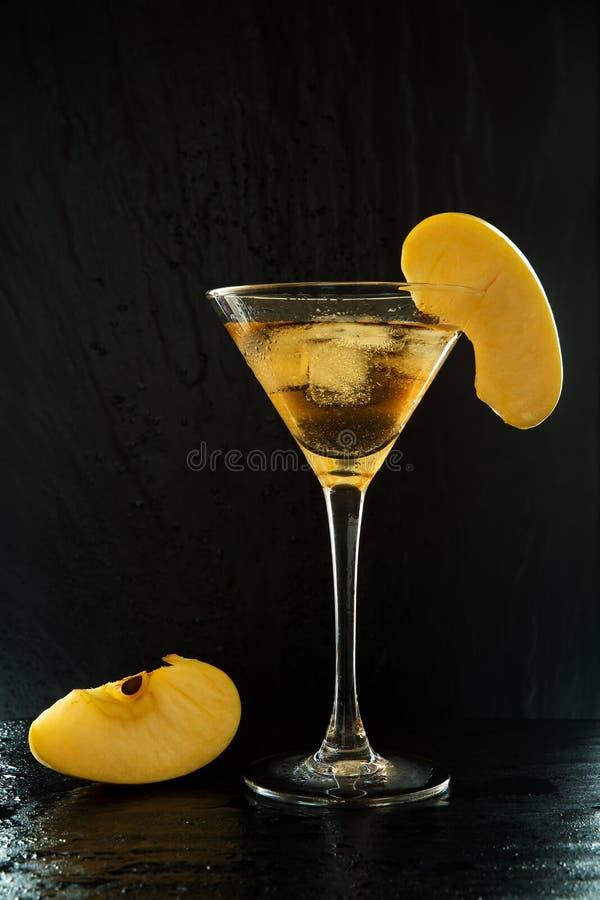 Ny sommarappletinicoctail i ett martini exponeringsglas med skivor för ett äpple på en svart, våt texturerad yttersida med vatten royaltyfri foto