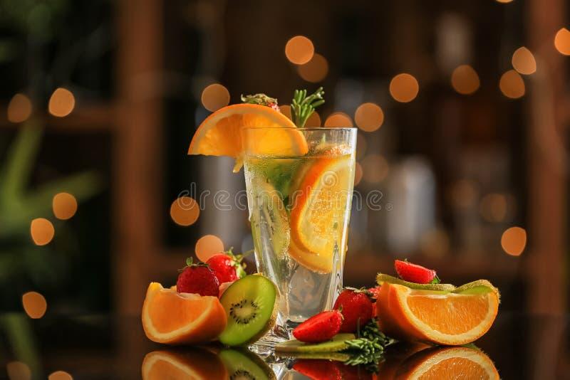 Ny sommarcoctail i exponeringsglas med frukter mot suddiga ljus arkivfoto