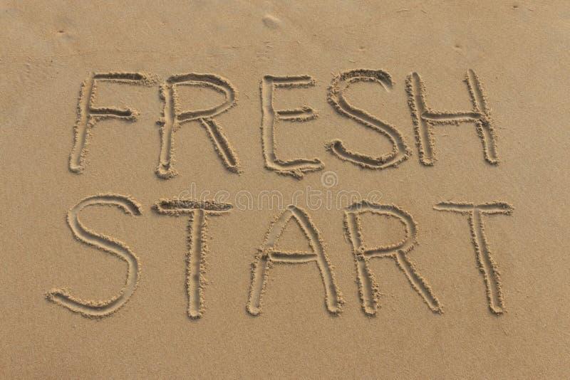 Ny start som är skriftlig i sanden arkivfoto