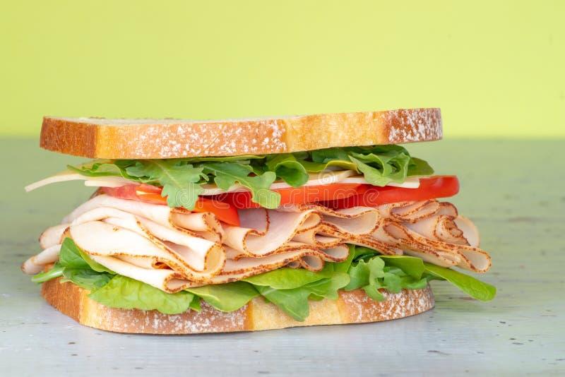Ny stor smörgås Turkiet skinka på ett vitt bröd med grönsallat, tomater och ost m?nga bakgrundsklimpmat meat mycket arkivfoto