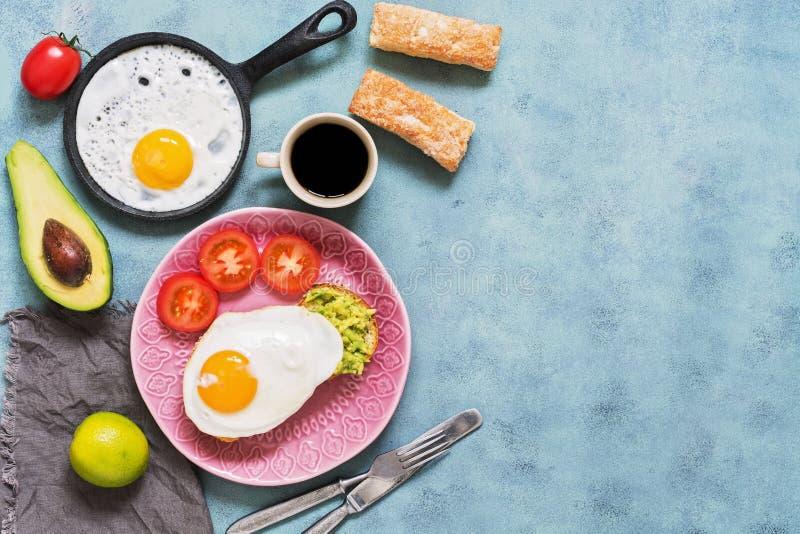 Ny sund frukost, förvanskade ägg, avokado, kaffe och bakelser på en blå bakgrund Bästa sikt, kopieringsutrymme fotografering för bildbyråer
