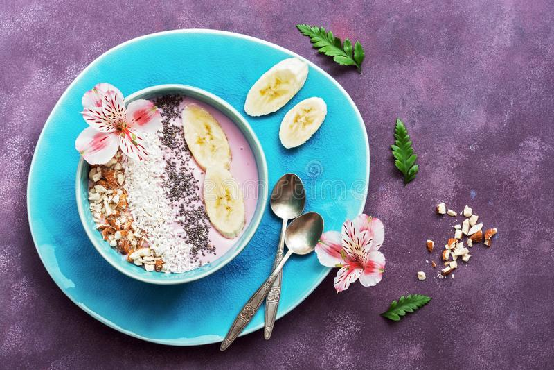 Ny sund frukost - yoghurt med bananen, mandel, kokosnötflingor, chiafrö i en blå bunke som dekoreras med blommor på en lila arkivbilder