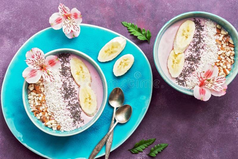 Ny sund frukost - yoghurt med bananen, mandel, kokosnötflingor, chiafrö i en blå bunke som dekoreras med blommor på en lila royaltyfri bild