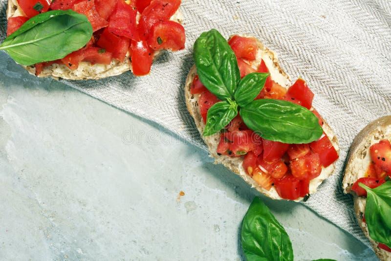 Ny tomatbruschetta italiensk mataptitretare med basilika fotografering för bildbyråer