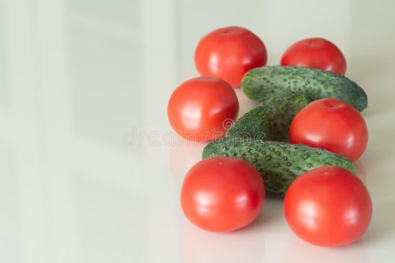 Ny tomater och gurka på ett vitt exponeringsglasköksbord Nya ingredienser för organisk mat Top besk?dar fotografering för bildbyråer