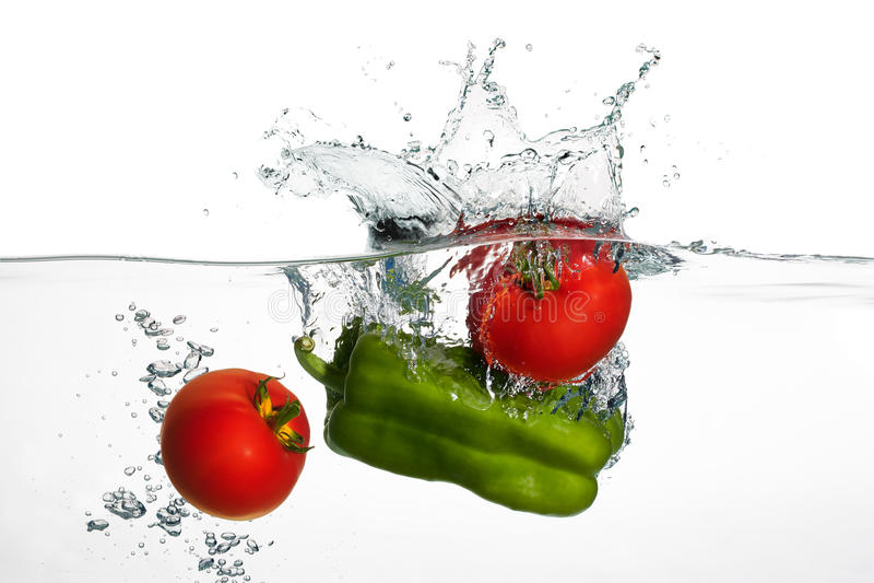 Ny tomater och paprikafärgstänk i vatten som isoleras på Whit royaltyfria bilder