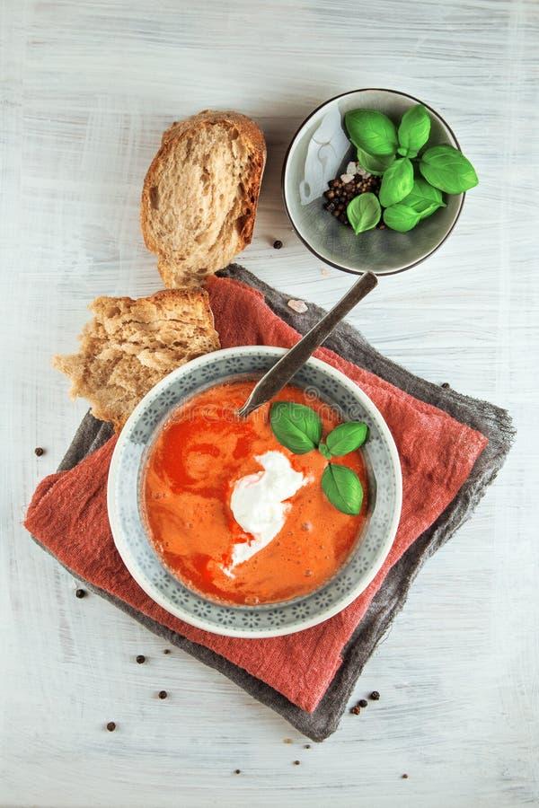 Ny tomatsoppa i en bunke med tomater och basilika på ett vitt köksbord arkivfoton