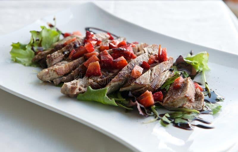 Ny tonfisk med jordgubbar i grå ljus bakgrund, sicialiian mat, italiensk mat, fisk i plattan, ny tonfisk, italienskt kök arkivbild