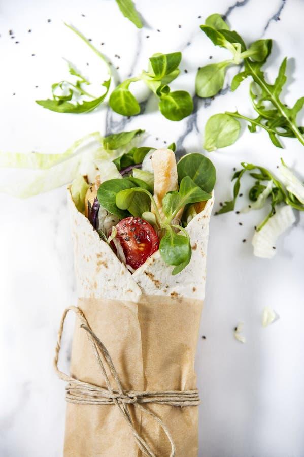 Ny tortillasjal med grönsaker och höna Bundet runt med brunt papper och rad arkivfoton