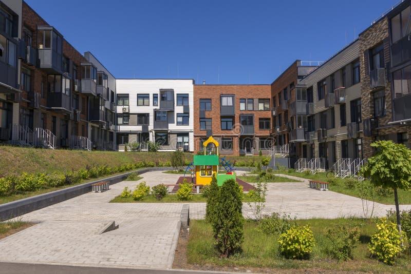 Ny tre-våning bostads- byggnad Lekplats i g?rden nytt bostads f?r omr?de royaltyfri foto
