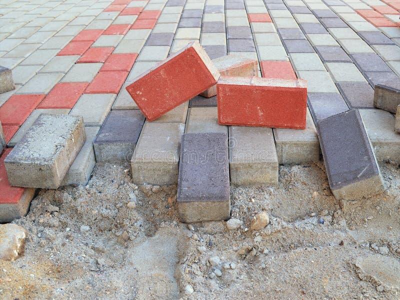 Ny trottoar som lägger med rektangulära förberedande tjock skiva av den gråa, blåa och röda coloen arkivfoton