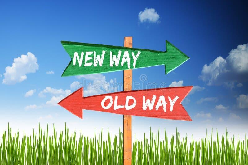 Ny väg vs gammal väg på träpilar med blå himmel arkivfoto