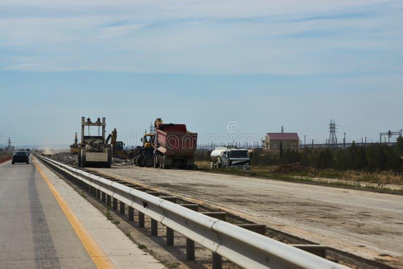 Ny vägkonstruktion med att asfaltera maskiner arkivbilder