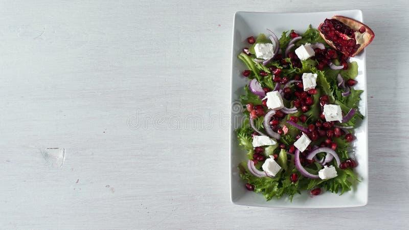 Ny vårsallad med fetaost, den röda löken och granatäpplefrö i den vita maträtten Bästa sikt, kopieringsutrymme royaltyfria foton